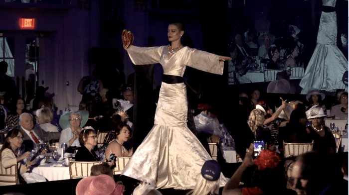 "A model adorns a dress premiered at ""Tea for Trump"" that designer Andre Soriano fashioned as a tribute to Trump's meeting with North Korean officials in Singapore. (Screenshot / YouTube)."