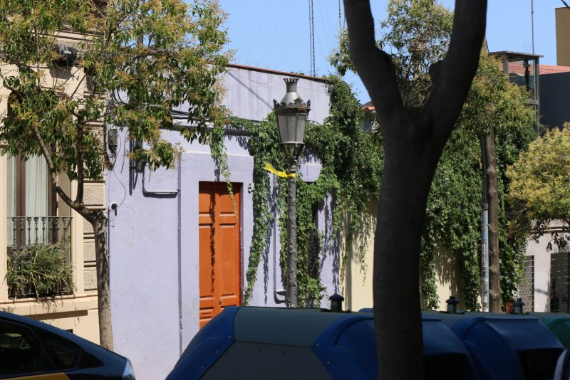 A light purple house with a lamppost with a yellow ribbon
