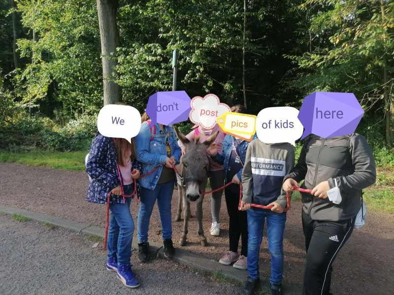 """Six kids holding the leads of a grey donkey. Their faces are covered with stickers that say """"We don't post pics of kids here"""""""