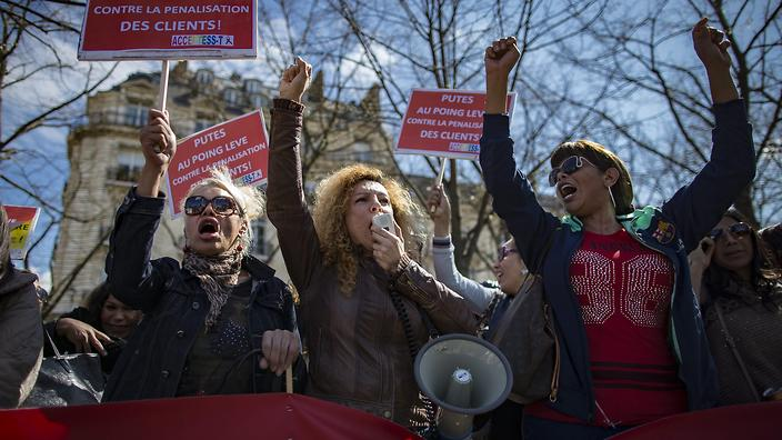 Transgender sex workers protest against a parliamentary vote to enforce the penalisation of solicitation, near the Assemblee Nationale (French parliament) in Paris, France, 06 April 2016. French parliament is seeking to pass a new bill which would penalise the clients of prostitutes - a move which angers NGO's prostitutes' associations, claiming such sanctions could push sex workers further into clandestine operations to circumvent the new sanctions. Signs read 'Prostitutes, fists raised in the air, against the penalisation of clients'. EPA/IAN LANGSDON