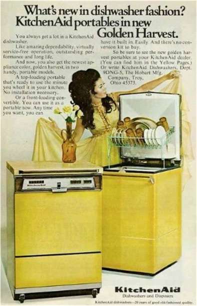 1970s Kitchen Aid dishwasher ad feat. photo of a white woman with elaborately coiffed hair posing dramatically in a golden-colored gown behind 2 dishwashers. On top of one sits a vase of flowers.