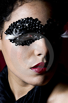 Stock Photos - Attractive young woman wearing a black gem mask