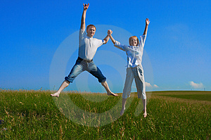 Free Stock Photography - Couple jumping in field