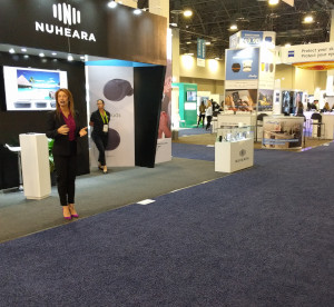 Woman with headset at CES giving presentation to empty aisle