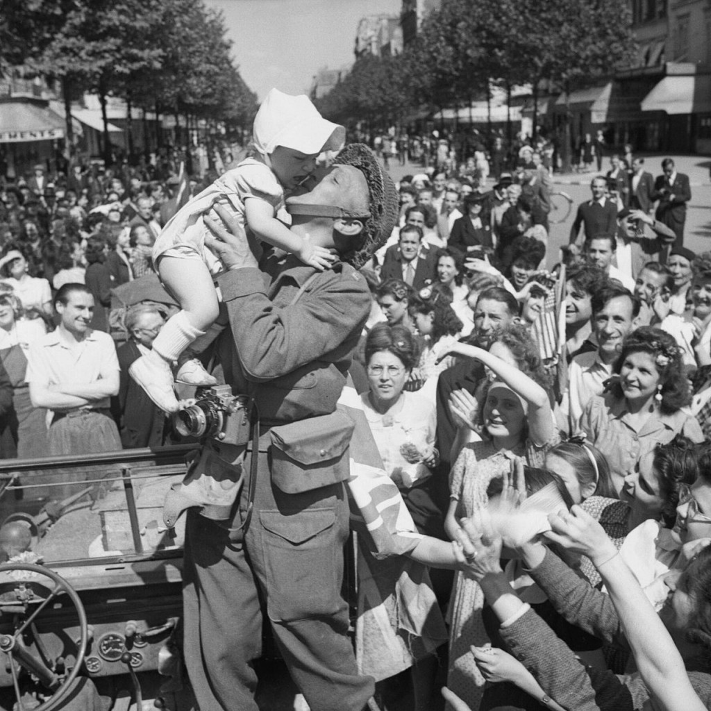 An AFPU photographer kisses a small child before cheering crowds in Paris, one day after liberation, 26 August 1944.