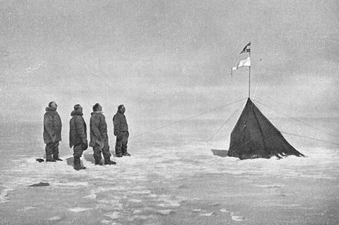 """Roald Amundsen, Helmer Hanssen, Sverre Hassel and Oscar Wisting (l–r) at """"Polheim"""", the tent was erected at the South Pole on 16 December 1911. The top flag is the Flag of Norway; the bottom is marked """"Fram"""". Photograph by Olav Bjaaland."""
