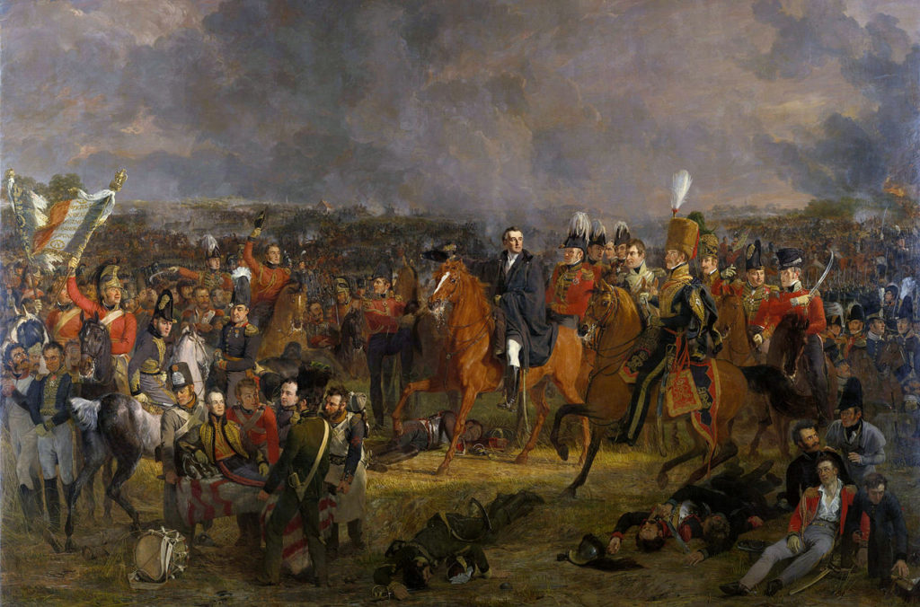 Jan Willem Pieneman: The Battle of Waterloo (1824). Duke of Wellington, centre, flanked on his left by Lord Uxbridge in hussar uniform. On the image's far left, Cpl. Styles of the Royal Dragoons flourishes the eagle of the 105eme Ligne. The wounded Prince of Orange is carried from the field in the foreground. Via Wikipedia.