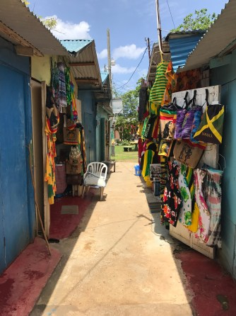 Photo of street market in Negril, Jamaica. Colorful bags and clothes hanging on walls.