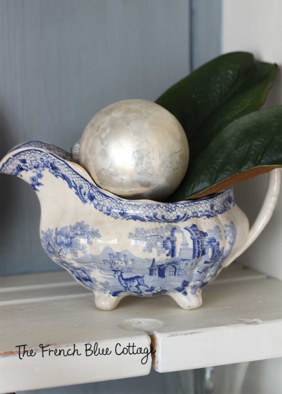 Blue and white gravy boat with vintage ornament and magnolia.