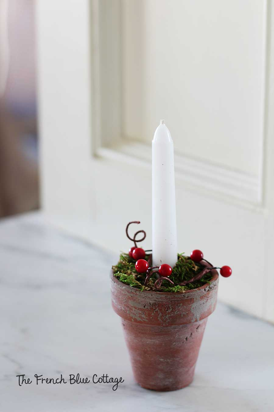 Faux red berries on a Christmas candle.