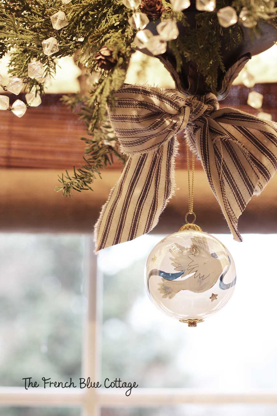 Chandelier with greenery and a blue ticking bow.