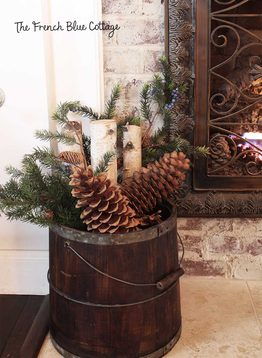 Birch logs, evergreens, and pinecones in large bucket by fireplace.
