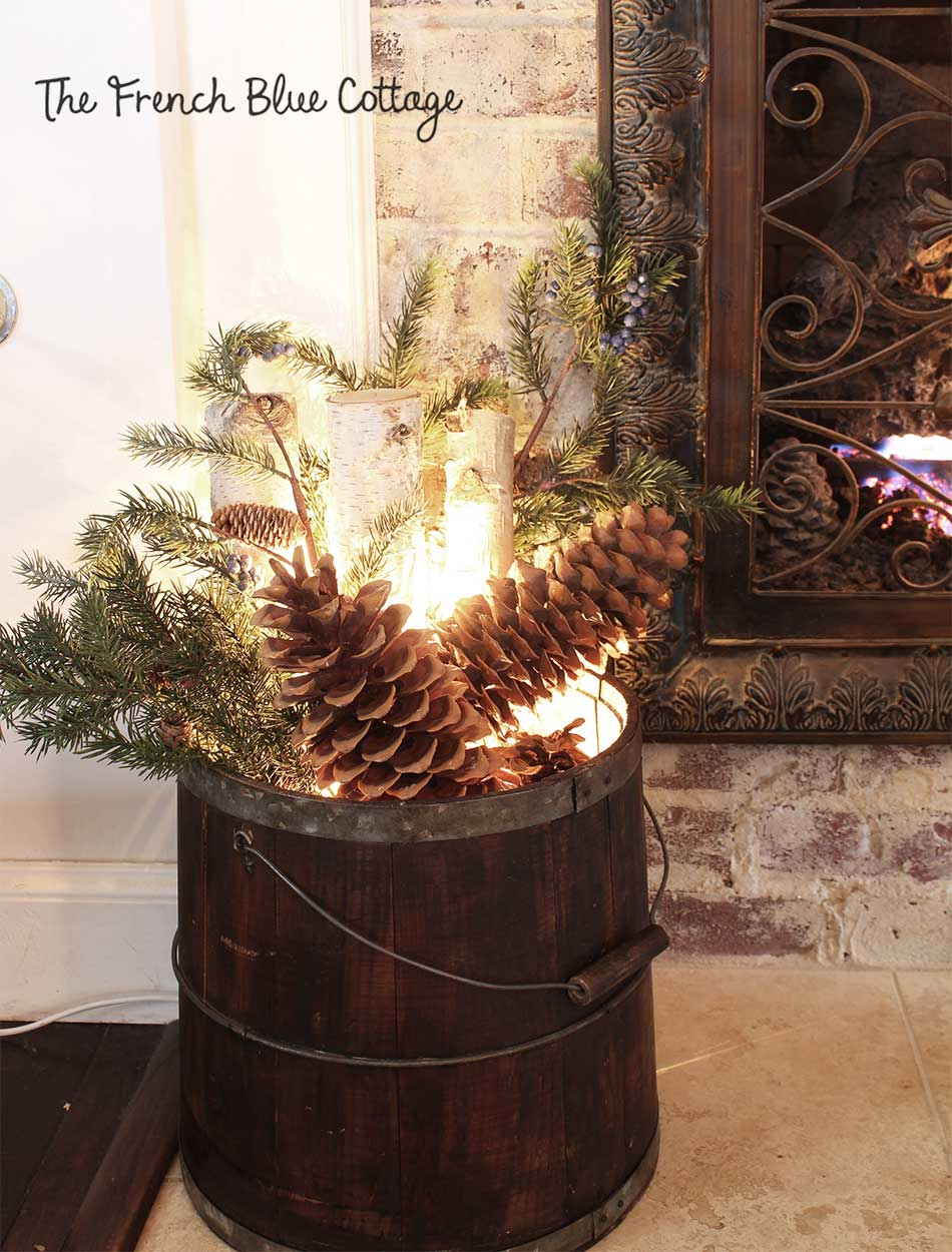 Fireplace bucket with birch logs and twinkle lights.