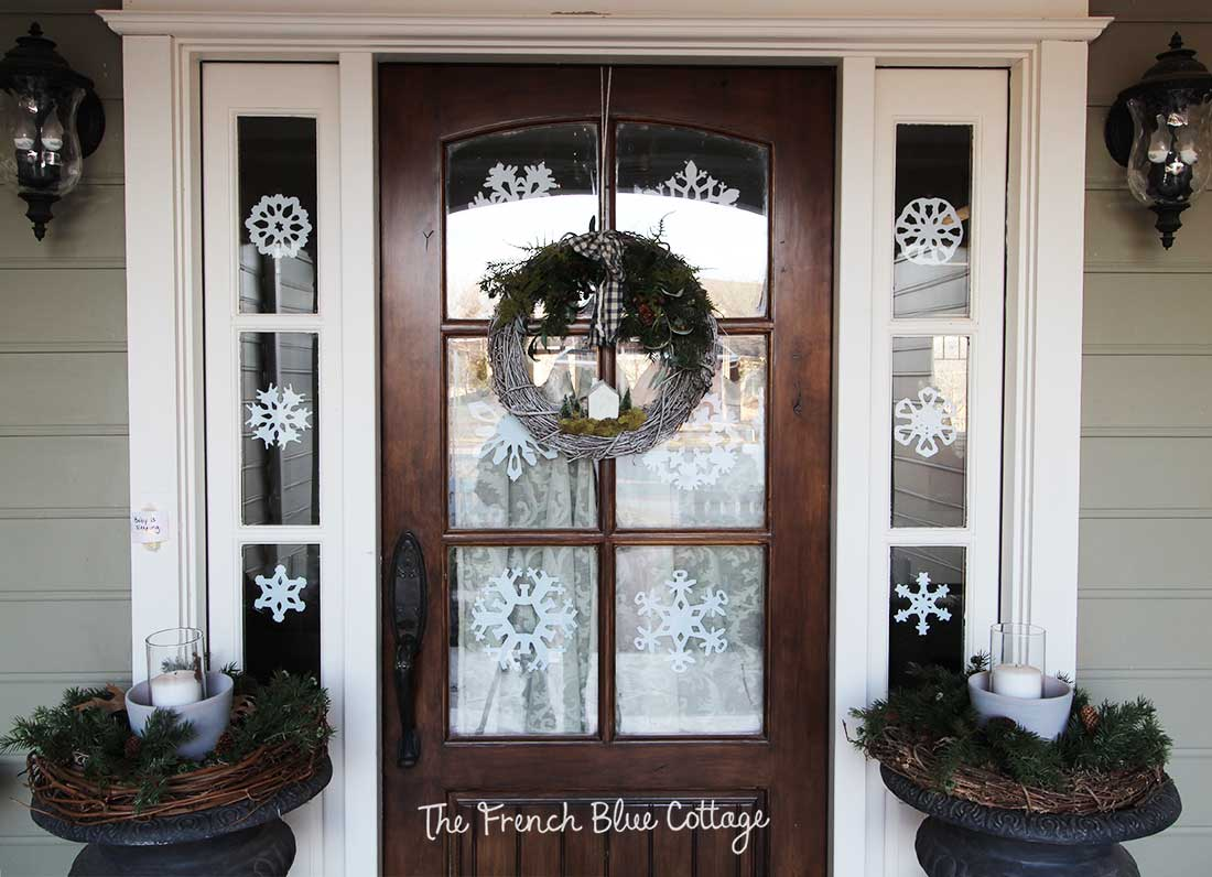 Front door and sidelights with paper snowflakes.
