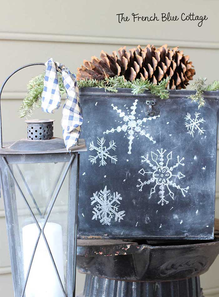 Chalkboard box on winter porch with snowflakes.