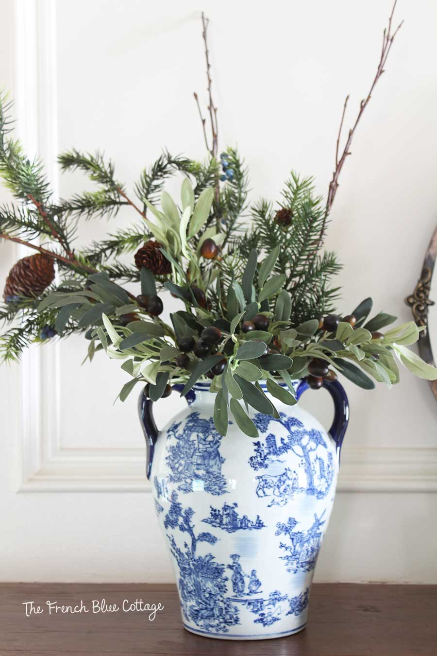 Winter greenery arrangement with olive branches.