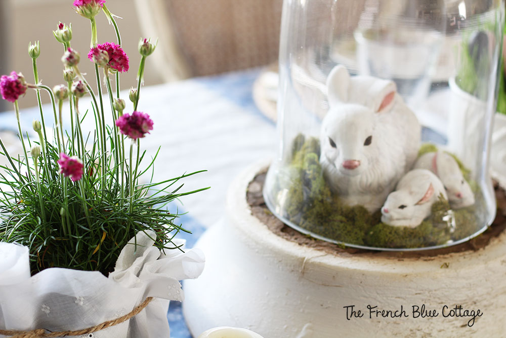 Bunnies sitting on an old wood column base and under a cloche.