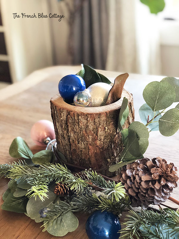 Dining room table with log centerpiece and blue ornaments.