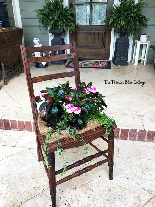 wood chair with flowers planted in the seat