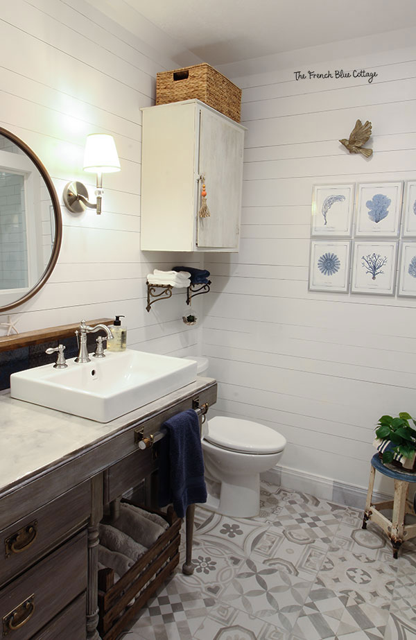 coastal farmhouse bathroom with chippy cabinet, round mirror, and sea fan art