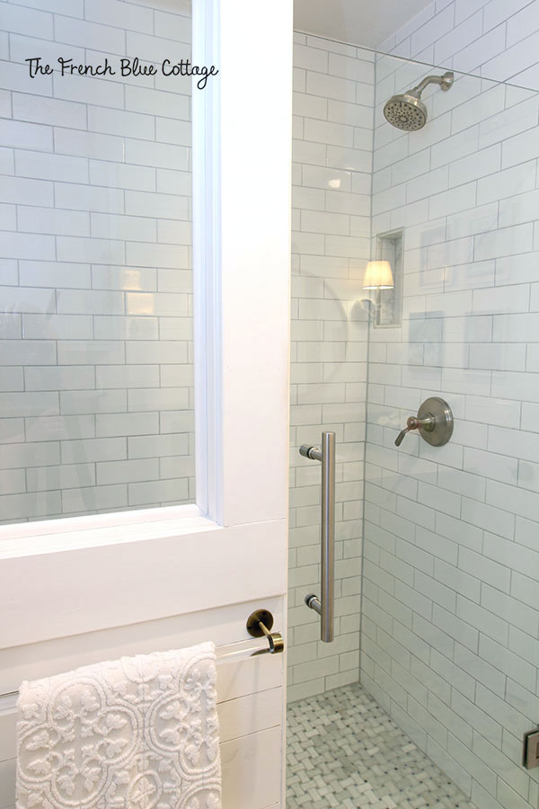 glass shower door with a half wall with a tempered glass window