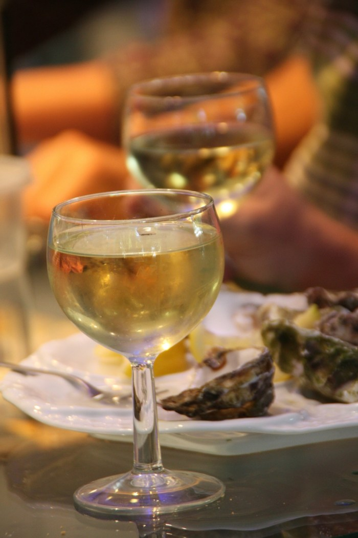 A glass of white wine with some oysters