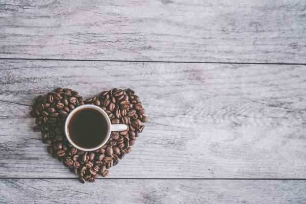 white ceramic mug filled with brown liquid on heart shaped coffee beans