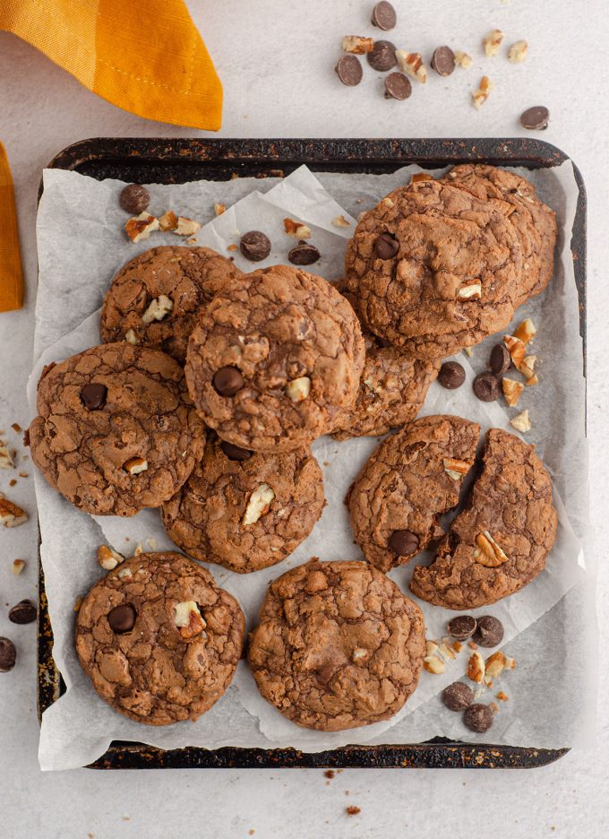 aerial photo of tray of brownie cookies with chocolate chips and nuts scattered around