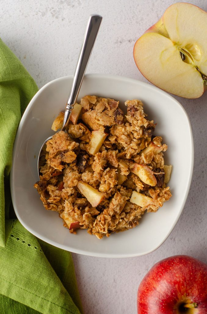 aerial photo of baked apple oatmeal in a white bowl with a spoon