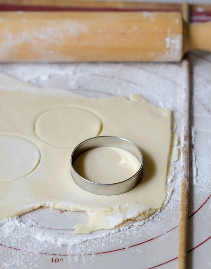 cut-out sugar cookie dough being cut into circles