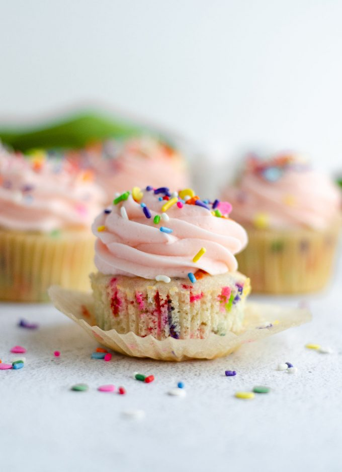 homemade funfetti cupcake with pink frosting and sitting in a wrapper that has been taken off