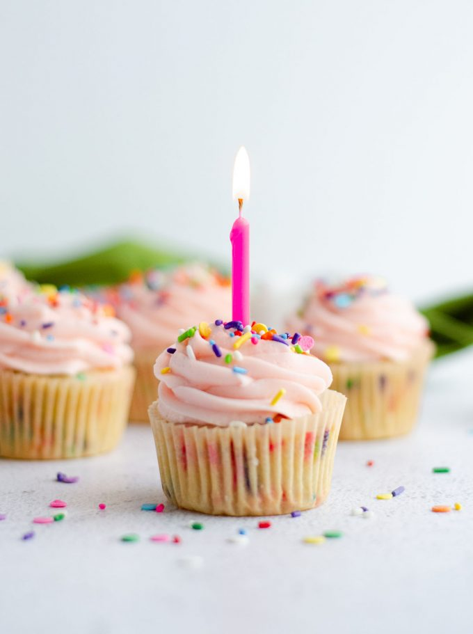 homemade funfetti cupcake with pink frosting and a lighted pink birthday candle