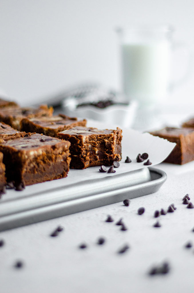 cut brownies and one with a bite taken out on parchment ready to serve with tongs, a glass of milk, and bowl of mini chocolate chips