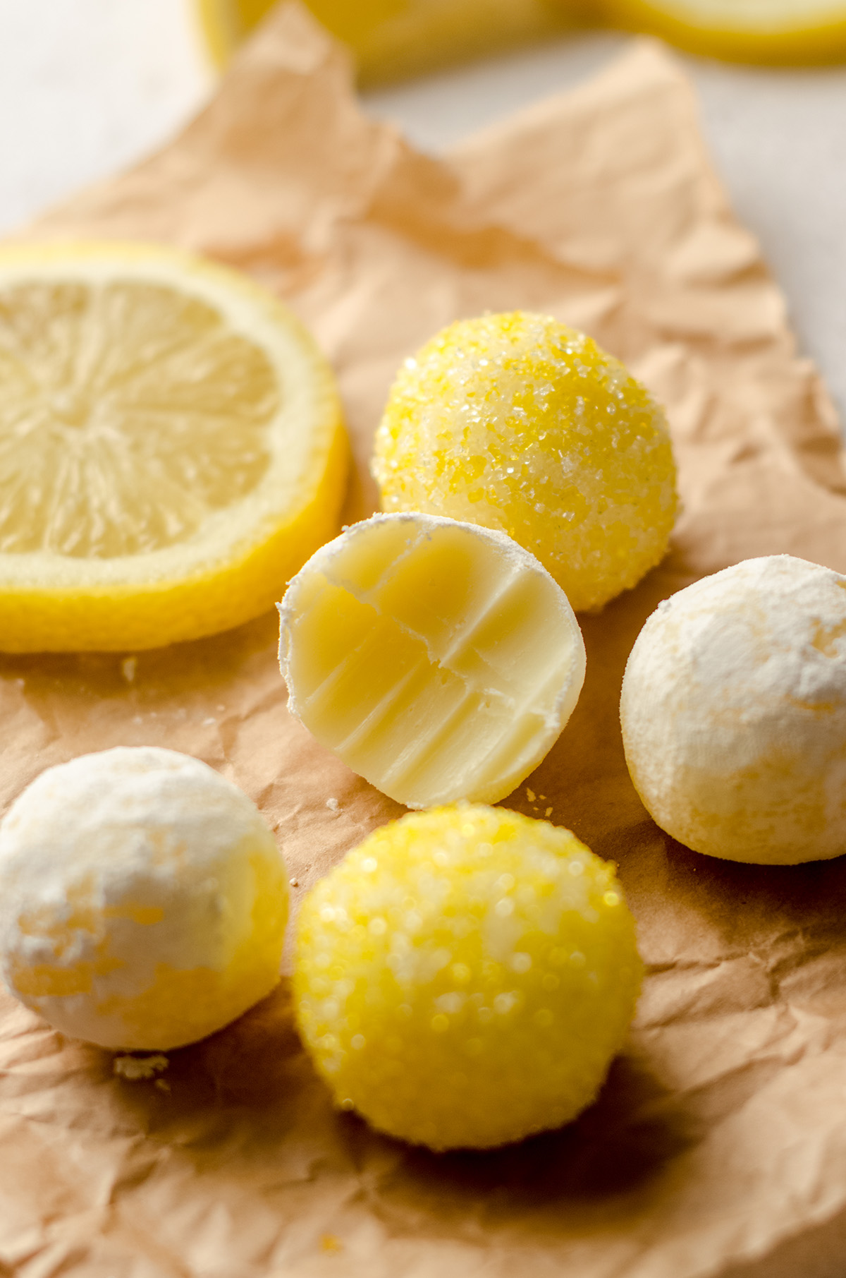 lemon truffles on parchment and one has a bite taken out of it