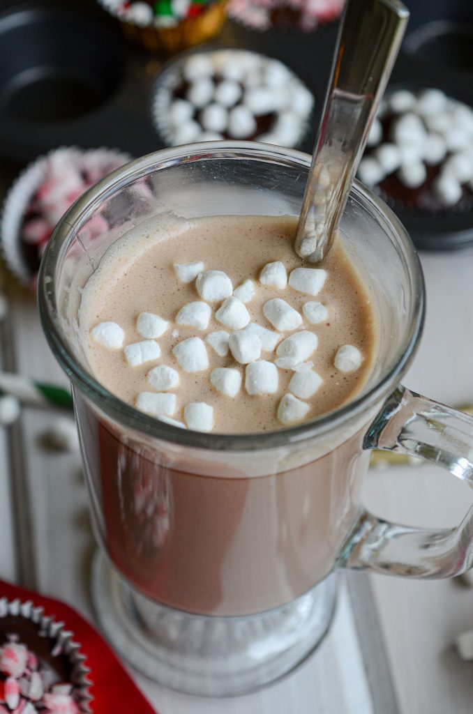 hot chocolate in a mug with a spoon and little mini marshmallows floating on top