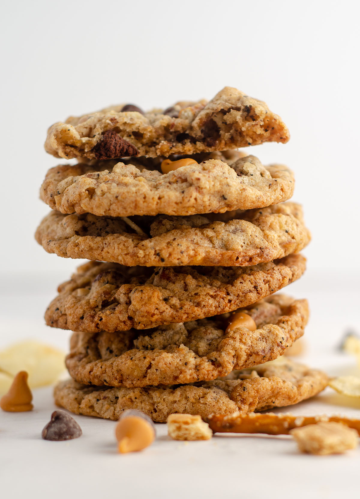 stack of compost cookies scattered with chips, pretzel pieces, chocolate chips, and butterscotch chips