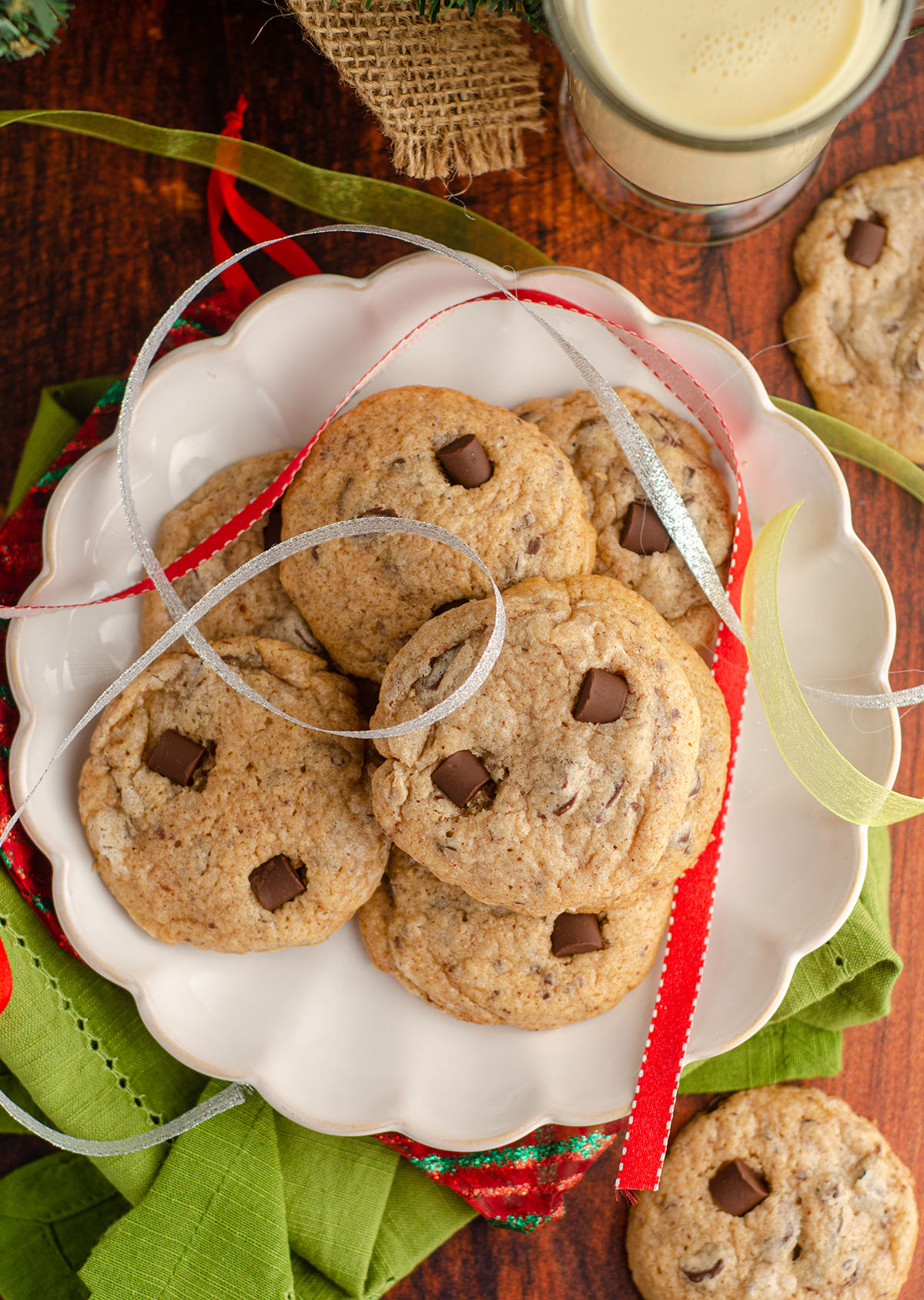 aerial photo of eggnog chocolate chunk cookies sitting on a plate with christmas ribbons around it