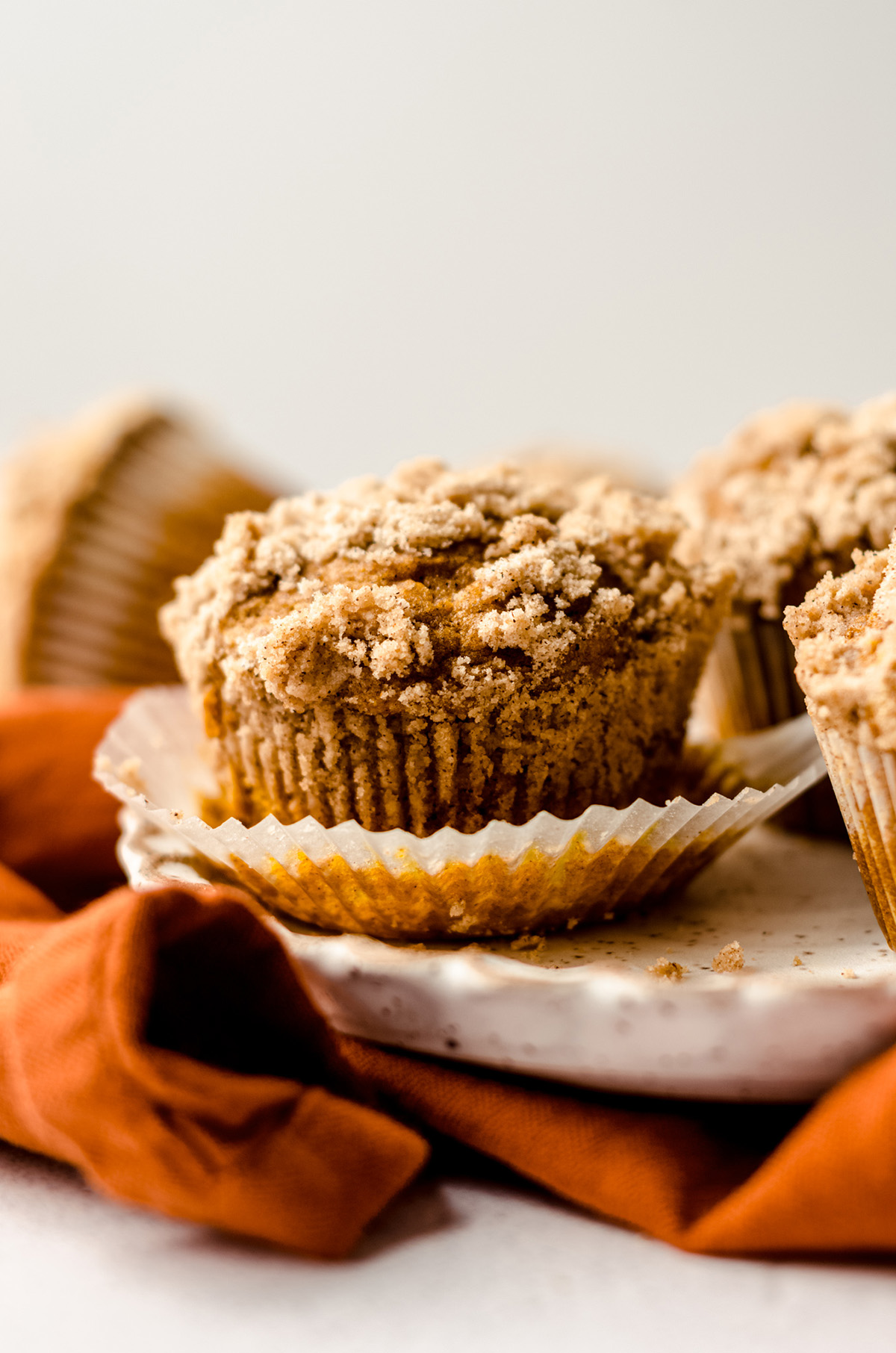 unwrapped pumpkin muffins on a plate