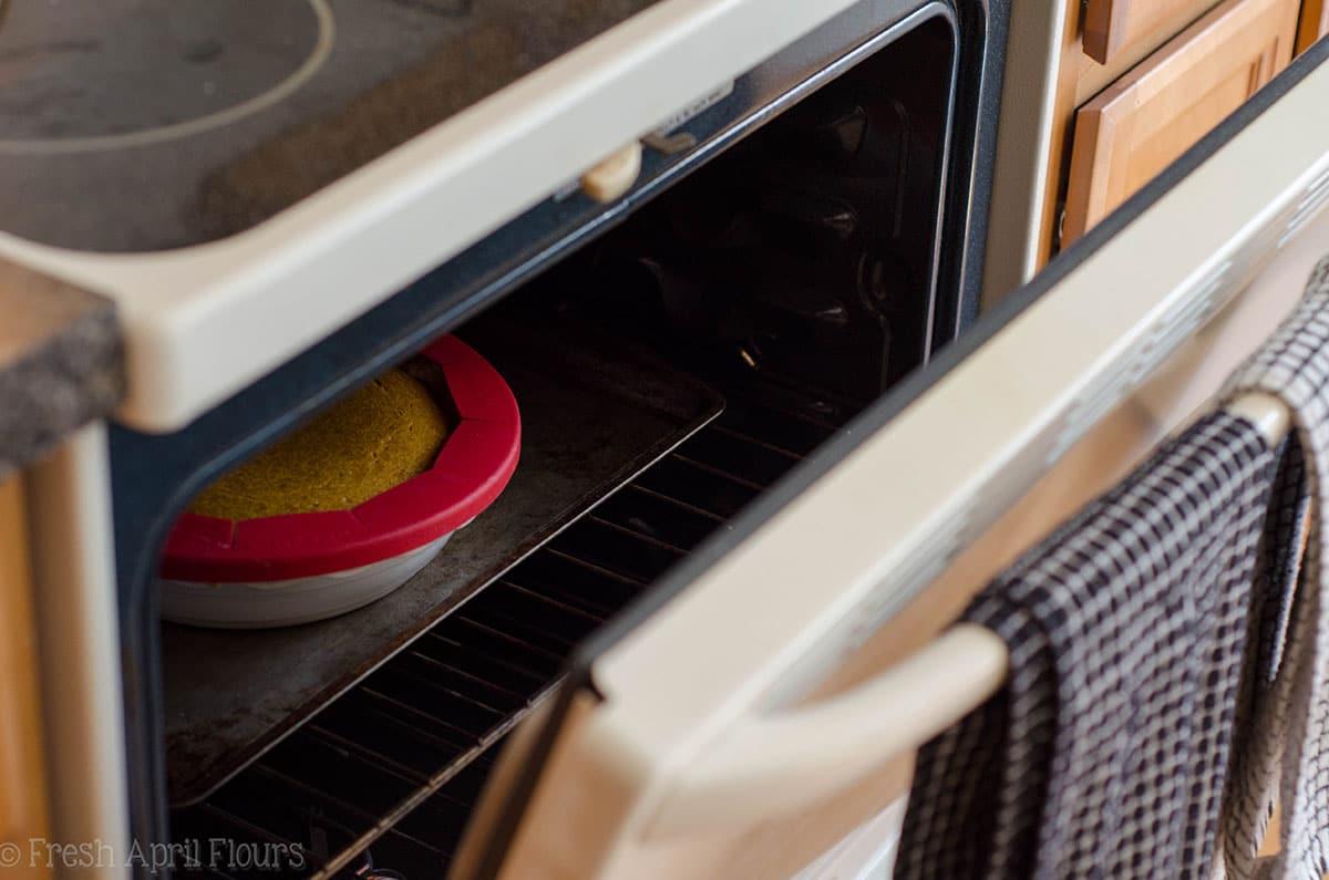 oven door sitting open with a pumpkin pie baking inside