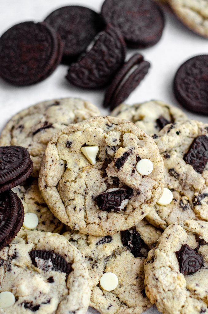 cookies and cream cookies in a pile with lots of oreos surrounding them