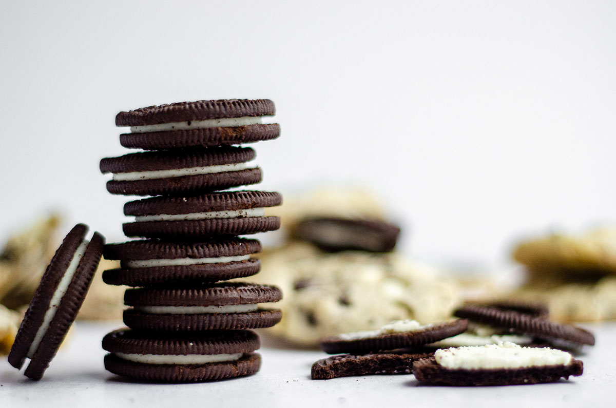 stack of oreos with cookies and cream cookies in the background