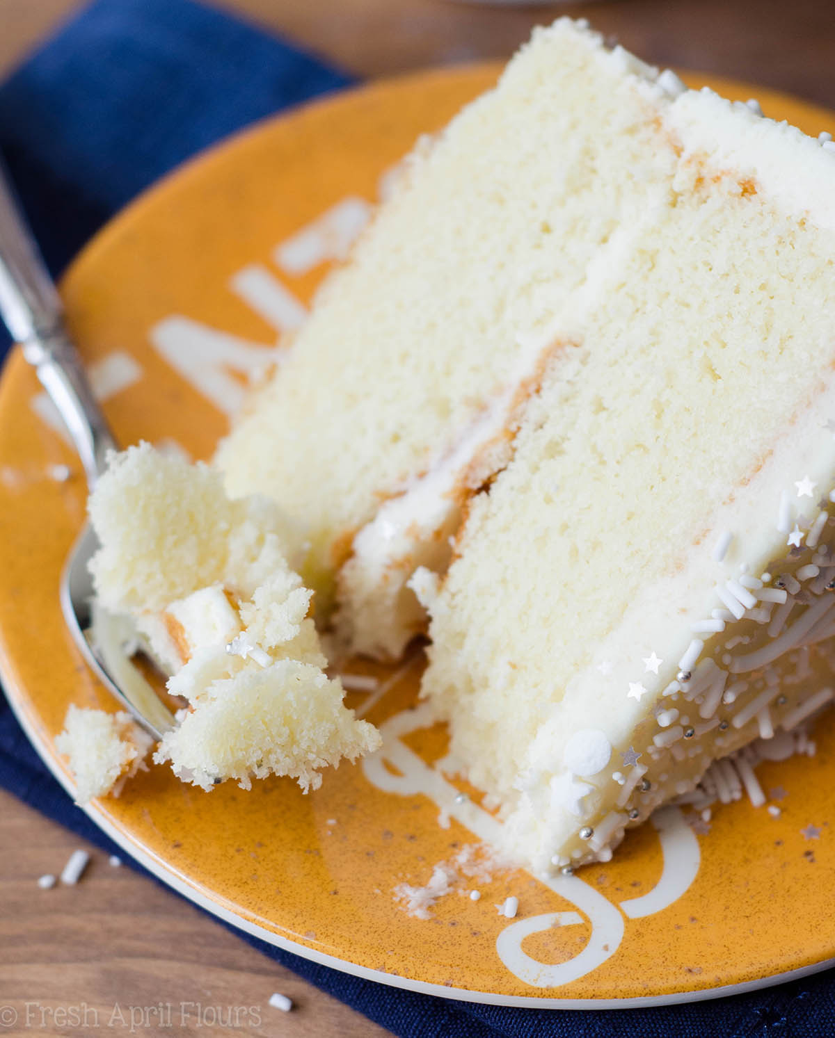 white layer cake with whipped cream buttercream sitting on a yellow plate with a fork full of a bite of cake