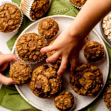 children's hands grabbing toddler muffins from a plate