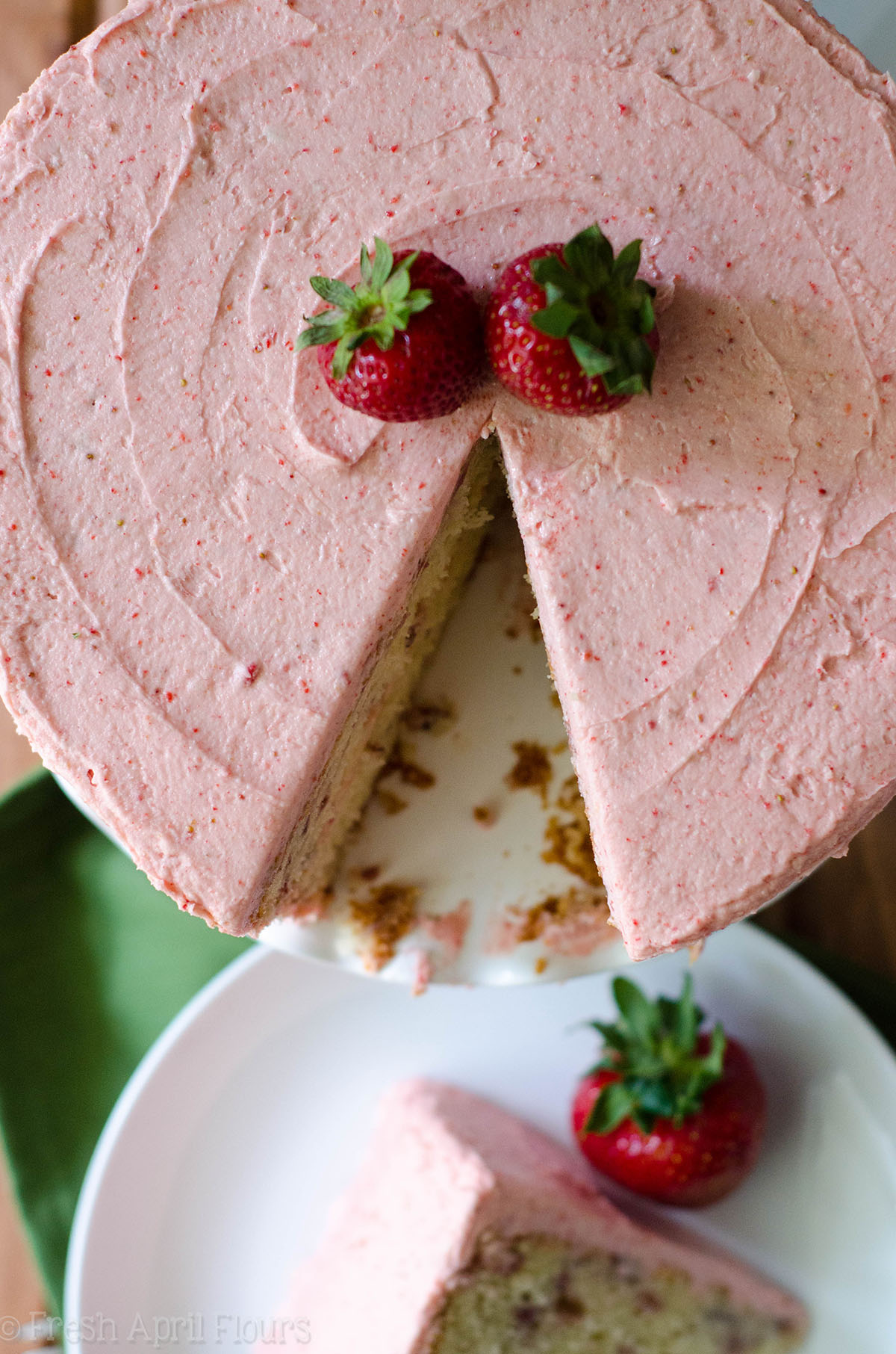 aerial photo of fresh strawberry cake with a slice cut out of it