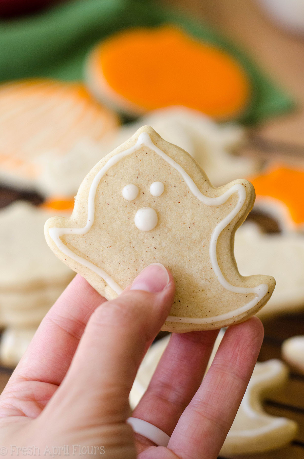 hand holding a ghost shaped pumpkin spice cut-out sugar cookies