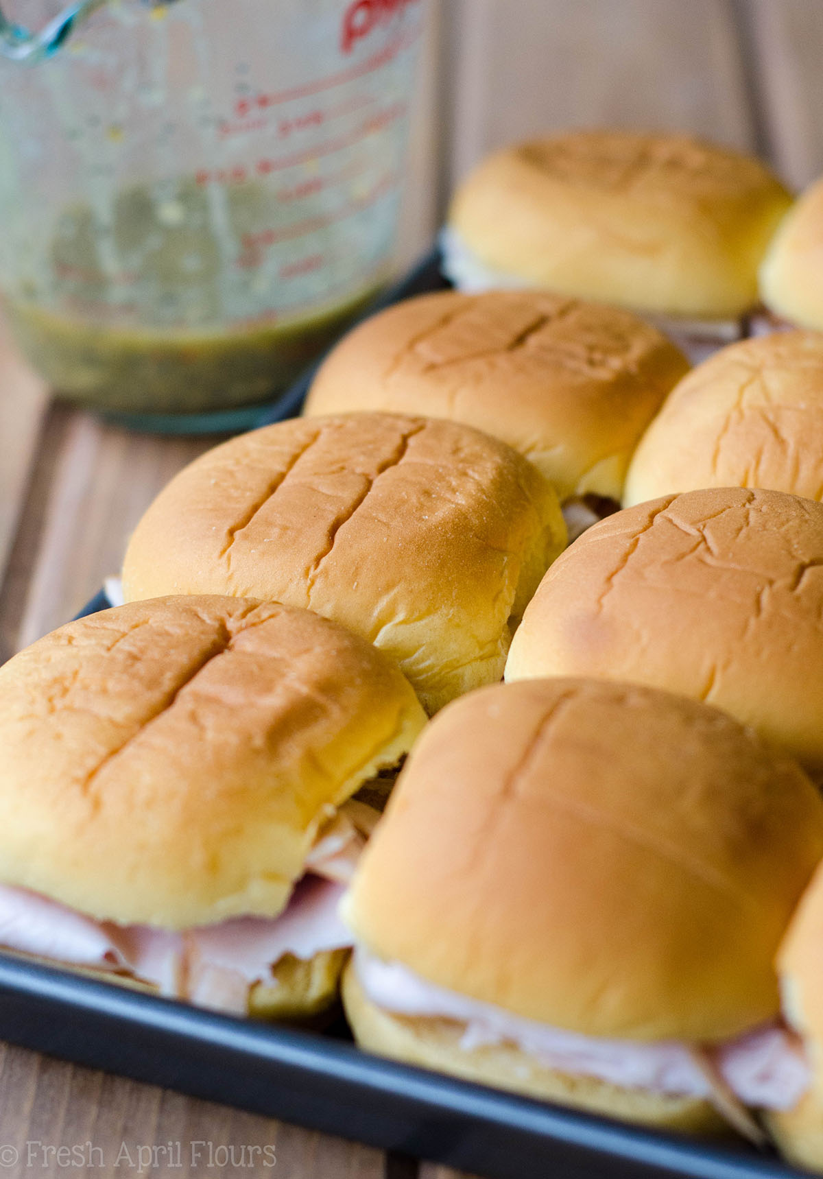 turkey and cheese sliders on a baking sheet ready to bake