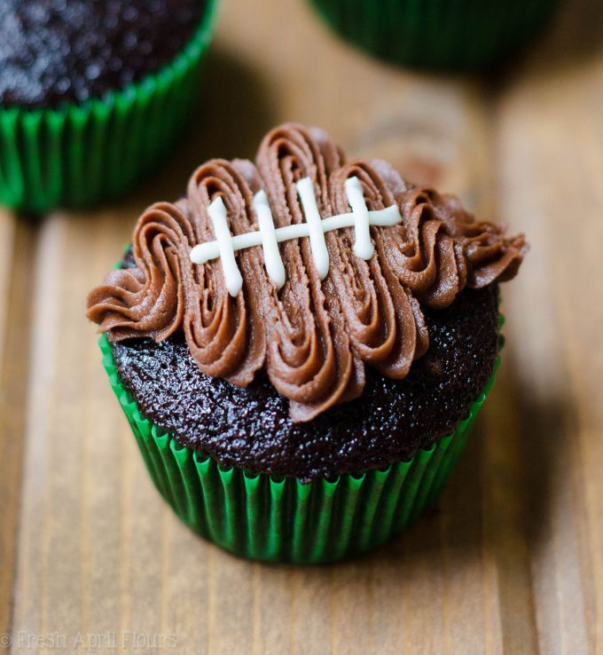 chocolate cupcake in a green cupcake liner with a chocolate frosting football piped on top to make football cupcakes