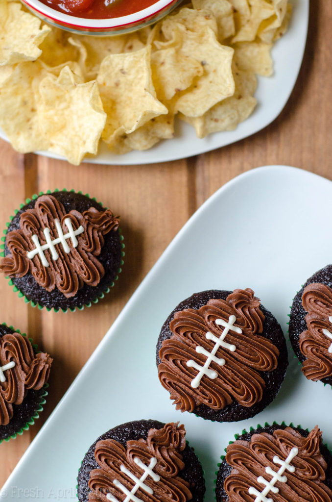 aerial photo of chocolate cupcakes in green cupcake liners with a chocolate frosting footballs piped on top to make football cupcakes