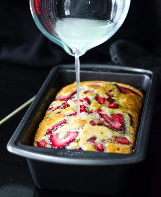 pouring lemon syrup onto strawberry lemonade quick bread