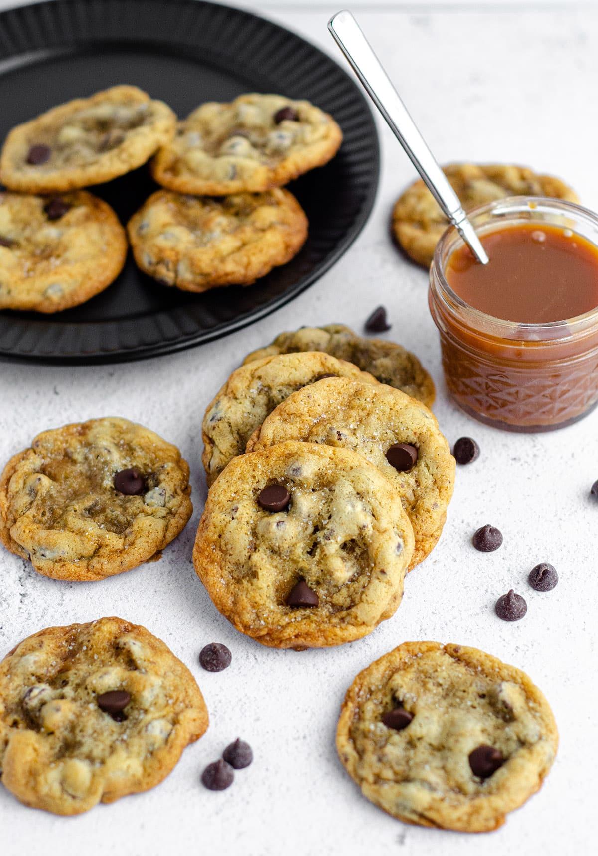 salted caramel chocolate chip cookies with a jar of salted caramel sauce